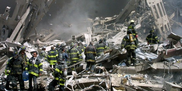 September 11, 2001 - Firefighters make their way through the rubble. Photo / AP