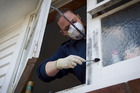 Crime scene attendant Esme Blair looks for fingerprints at a burglary in Mt Roskill. PHOTO / FILE