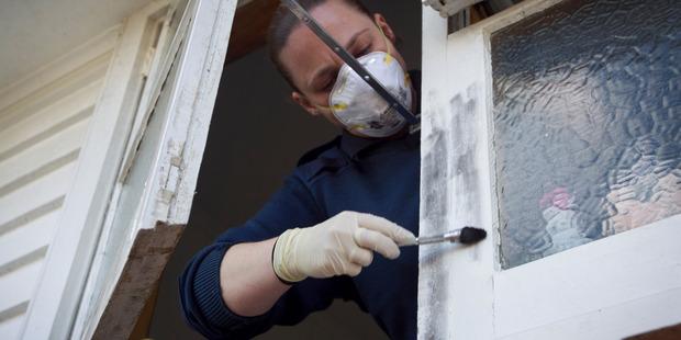 Crime scene attendant Esme Blair looks for fingerprints at a burglary in Mt Roskill. PHOTO / FILE