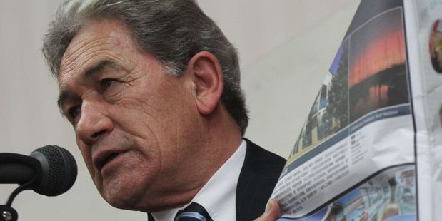 NZ First leader Winston Peters holds a real estate magazine targeting Chinese buyers at a meeting in Masterton. PHOTO/FILE