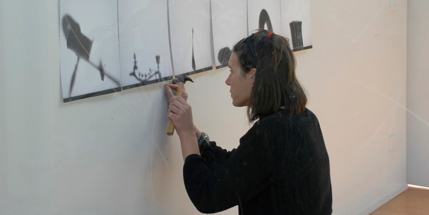 Cathy Tuato'o Ross sets up the moving Shadow Collection exhibition at NorthTec's Geoff Wilson Gallery.