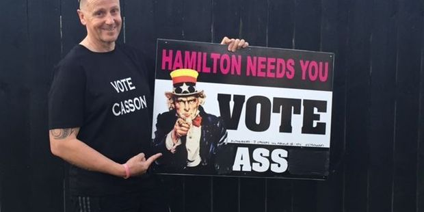 Mayoral candidate James Casson with his graffitied sign.