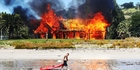 The mansion at Boatshed Bay, Waiheke Island,  formerly linked to  developer Mark Hotchin, is torched for a firefighting exercise. Photo / Doug Sherring