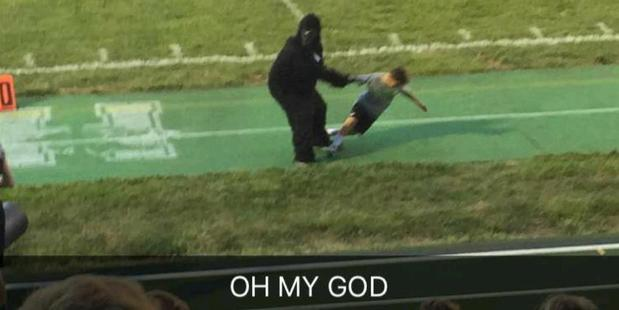 A man in a gorilla costume swings a child by the arm at a Cincinnati school. Photo / Imgur, TheAmazingSky