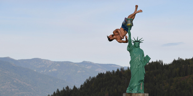 Jacob Clad, 22, performs a flip into Lake Pend Oreille near a replica of the Statue of Liberty in Sandpoint, Idaho. Photo / The Washington Post