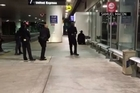 Los Angeles airport officials say a false report of gunshots that sent panicked travelers fleeing came right after officers, with guns drawn, detained a man dressed in black and carrying what he claims in the video is a plastic sword.