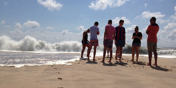 Beachgoers stand at the edge of the water in Bridgehampton, New York, on the southeastern shore of Long Island. Photo / AP