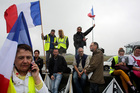 Demonstrators hold French flags as truckers block the highway near Calais, northern France. Photo / AP