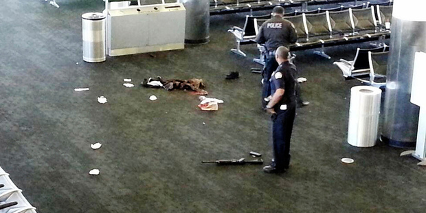 Police officers stand near a weapon inside Terminal 2 at Los Angeles International Airport after a shooting incident in 2013. Photo / AP