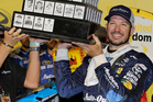 Martin Truex Jr. holds his trophy in Victory Lane after winning the NASCAR Sprint Cup Southern 500. Photo / AP