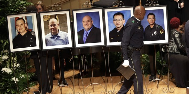A member of the Dallas Police Choir passes the portraits of five fallen officers before a memorial service at Morton H. Meyerson Symphony Center in Dallas on July 12. Photo / AP