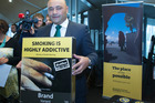 Associate Health Minister Sam Lotu-Iiga with an example of the new plain-packaging cigarette packet at the announcement in Wellington. Photo / Mark Mitchell
