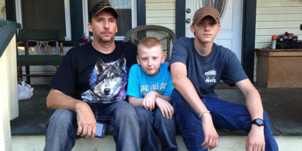 James Phillips with his sons Carter, centre, and Jayson on the porch outside their rental home. Photo / AP