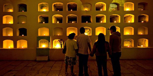 A family pauses to view candles lighting the crypts of San Miguel cemetery in Oaxaca, Mexico. Photo / Getty Images