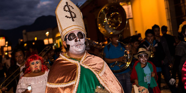 Costumed revelers parade through the streets of Oaxaca. Photo / Getty Images