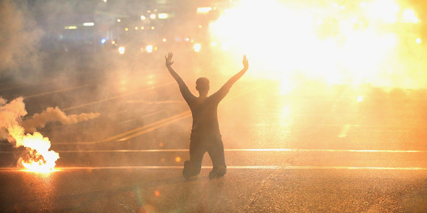 Tear gas reigns down on a woman kneeling in the street with her hands in the air after a Black Lives Matter demonstration in the U.S. Photo / Getty