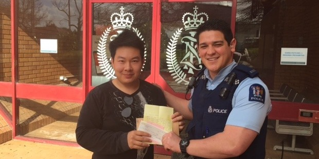 Officer in charge of the food caravan theft case Constable Isaac Teleiai hands over a $1000 donation from a member of the public to Gritsaru 'Ize' Janshinorat, the caravan owner. Photo/NZ Police