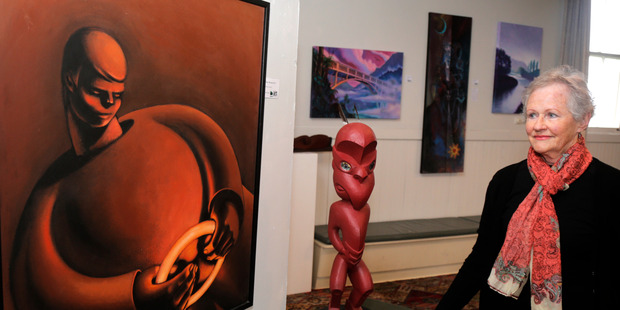 Wanganui Arts Society's Jeanette Cutten checks of the work of Taumarunui Arts Society's Mark Tyrrell and James Cannon. The two groups are exhibiting each other's work this month. Photo/ Bevan Conley