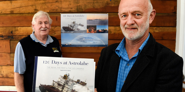 Captain Kevin Judkins and his book offering an eye witness view of the Rena salvage. Also pictured is Grumpy's Gallery owner Bob Ricketts.  Picture/George Novak