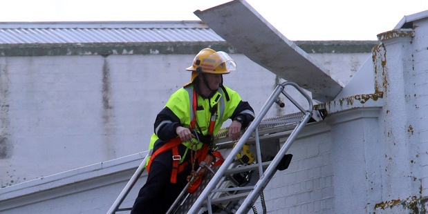 A firefighter secures loose flashing in Whanganui's Guyton St. PHOTO/ STUART MUNRO