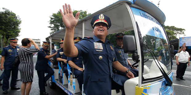 Philippine National Police chief, Ronald Dela Rosa, waves before boarding a vehicle at Camp Crame police headquarters in suburban Quezon city, north of Manila. Photo / AP
