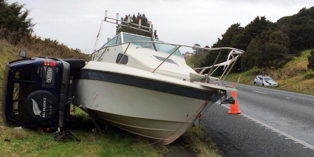 A 4WD and boat narrowly missed an abandoned car (right) involved in a crash earlier in the day on State Highway 1 near the Ruakaka turnoff. Photo / Jeff D' Ath