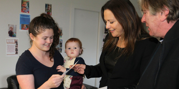 Rachel Burt with daughter Elliot, 11 months, receiving the relaxation package from the manager of The Dome in Napier Ailne Bradley and Havelock North Business Association president Sam Jackman. Photo / Duncan Brown