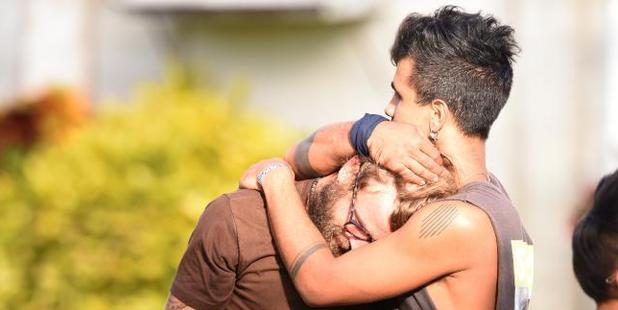 Backpackers comfort each other outside the Home Hill Backpackers after three people were stabbed. Photo / Zak Simmonds, News Corp