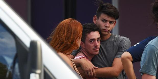 Backpackers comfort each other outside the Home Hill Backpackers after three people were stabbed. Photo / Zak Simmonds News Corp
