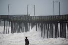 Lucille Rang, who is originally from Canada but moved to Virginia Beach recently, looks at the waves at a fishing pier in Virginia Beach. Photo / AP