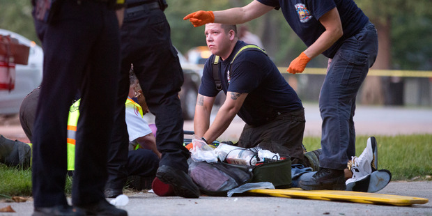The Chicago Fire Department work on a gunshot victim at the scene of a double shooting in Ogden Park, in the Englewood neighbourhood of Chicago on Monday. Photo / AP