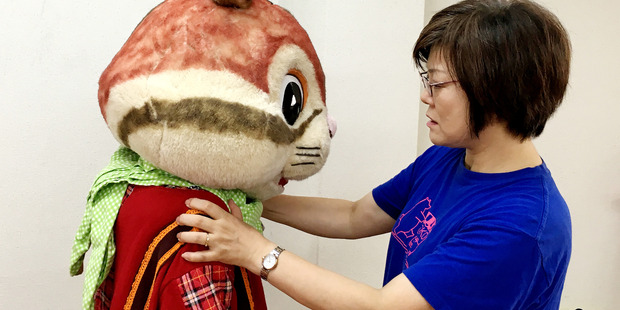Choko Ohira, who runs the Mascot Actors' School, helps Yuko Mura with her squirrel costume. Mura, who is 19, started at the school in January and hopes to become professional. Photo / Washington Post