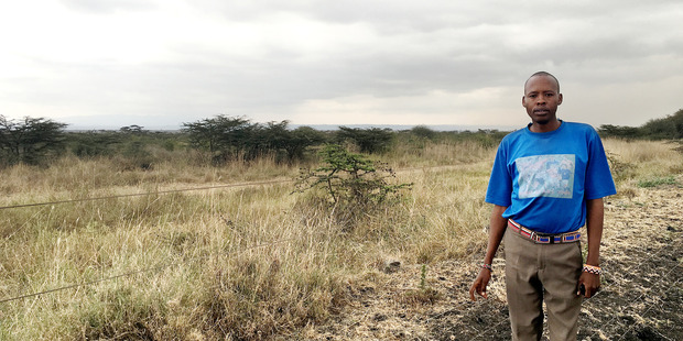 Simon Saigilu stands next to an electric fence that often fails, allowing lions from the nearby reserve to enter his village. Photo / The Washington Post / Kevin Sieff