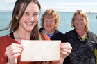 Maria Gibney, left, is reunited with the message in a bottle she wrote as a 10-year-old with the two ladies who found it, Cheryl Baird, centre, and Sharon Gomulski. Photo / Andrew Board