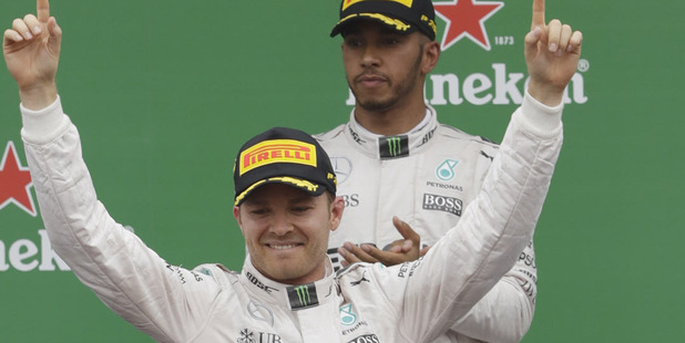 Mercedes driver Nico Rosberg of Germany, left, celebrates as second placed Mercedes driver Lewis Hamilton of Britain applaudes on the podium the Italian Formula One Grand Prix. Photo / AP