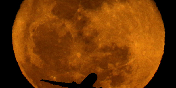 A waning moon rises in the distance as a passenger jet takes off. Photo / AP