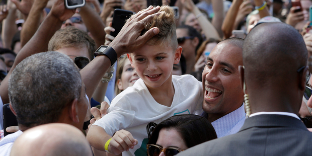 President Barack Obama musses a boys hair as he greets people in the audience at a campaign event for Democratic presidential candidate Hillary Clinton in Philadelphia. Photo / AP