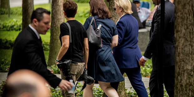 Democratic presidential candidate Hillary Clinton, second from right, departs after attending a ceremony at the September 11 memorial, in New York. Photo / AP