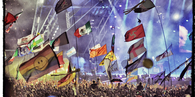 A general view of flags in the crowd as the Rolling Stones perform on the Pyramid stage during day 3 of Glastonbury. Photo / Getty