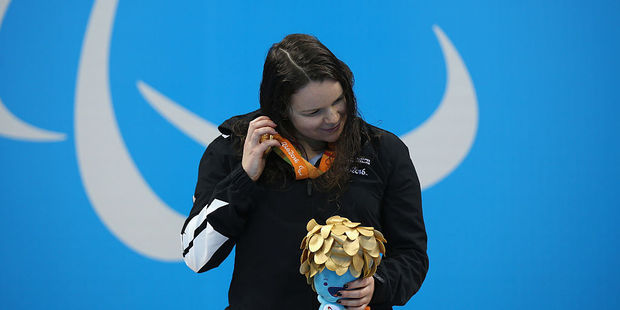 Gold medalist Mary Fisher of New Zealand listens to the sound of the medal on the podium. Photo / Getty Images