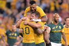 Bernard Foley of the Wallabies is congratulated by team mates after scoring a try. Photo / Getty