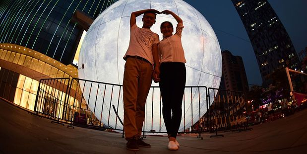 A couple pose with a giant inflatable moon model at Joy City, Yantai, Shandong Province of China ahead of Mid-Autumn Festival. Photo / Getty