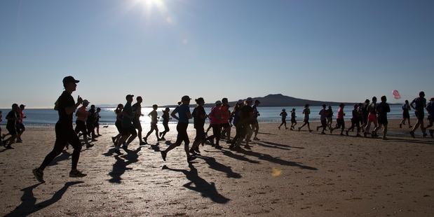 Runners make their way along Takapuna beach during the North Shore Marathon. Photo / Brett Phibbs