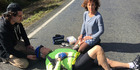 A cyclist lies in Woodcocks Rd, Warkworth, on Saturday after being found  unconcious in the road. On the right is  Sue O'Callaghan. Photo / Supplied