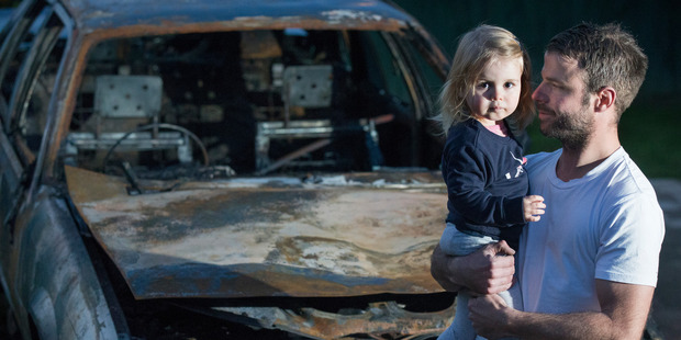 Adam Holt and two-year-old daughter Ava Holt, stand in front of Holt's burnt out 1987 Holden Calais that caught fire while Holt was driving down Auckland's Pakuranga Highway. Photo / Nick Reed