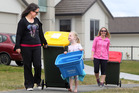 NEW: Erin Jarmey (left) wheels a new bin with neighbour Chloe de Loryn, 5, and Chantelle Ward in the back. PHOTO/BEN FRASER
