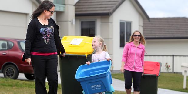 Loading NEW: Erin Jarmey (left) wheels a new bin with neighbour Chloe de Loryn, 5, and Chantelle Ward in the back. PHOTO/BEN FRASER