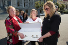 March for Moko members, from left, Leigh Woodman, of Wellington, Haylee Heke, Waikato, and Jayne Walker, Christchurch, with the petition in a white coffin at Parliament. Photo / Mark Mitchell