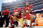 San Francisco safety Eric Reid and quarterback Colin Kaepernick kneel during the national anthem. Photo / AP