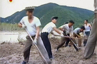 North Korean workers build levees along a river bank. Photo / AP